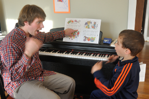 Photograph of Bram helping a young student through kinesthetic learning techniques.